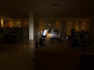 Woman working late at night in a dark office.
