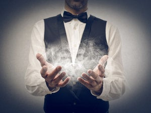 Magician with hands extended and smoke coming from hands