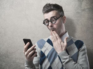 Goofy hipster looking at smartphone with hand raised to mouth