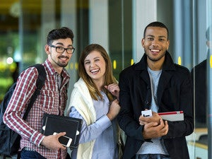 Multi-ethnic group of university students at college with school gear and gadgets.
