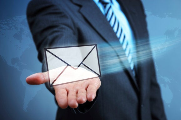 man in suit holding virtual email letter