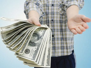 young man in plaid shirt holding pile of cash money