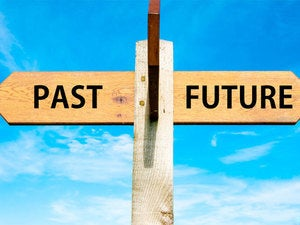 Wooden street sign with past and future going in two directions