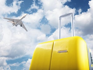 Yellow luggage with airplane and sky