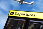 Airport departure sign with airplane flying over